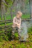 Petit garçon éteignant un feu de camp Photographie stock libre de droits