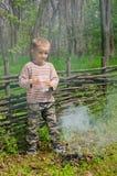 Petit garçon éteignant un feu de camp Photos libres de droits