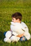 Petit garçon étreignant l'ours de nounours tout en se reposant sur l'herbe image stock