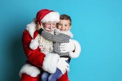Petit garçon étreignant Santa Claus authentique images stock