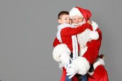 Petit garçon étreignant Santa Claus authentique photo stock