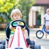 Petit garçon actif conduisant la voiture de pédale dans le jardin d'été Photos stock
