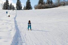 Petit garçon adorable avec la veste bleue et un casque, skiant photographie stock libre de droits