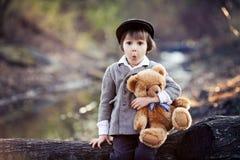 Petit garçon adorable avec son ami d'ours de nounours en parc Photographie stock