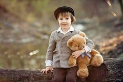 Petit garçon adorable avec son ami d'ours de nounours en parc Photos libres de droits
