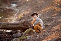 Petit garçon adorable avec son ami d'ours de nounours en parc Photo stock