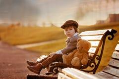 Petit garçon adorable avec son ami d'ours de nounours en parc Image stock