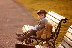 Petit garçon adorable avec son ami d'ours de nounours en parc Photo libre de droits