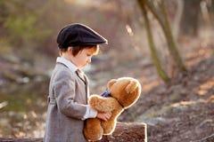 Petit garçon adorable avec son ami d'ours de nounours en parc Images libres de droits