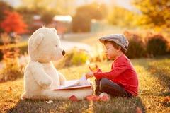 Petit garçon adorable avec son ami d'ours de nounours en parc sur le su Photographie stock libre de droits