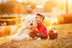 Petit garçon adorable avec son ami d'ours de nounours en parc sur le su Photos stock