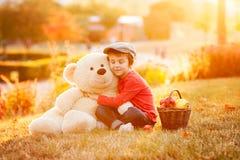 Petit garçon adorable avec son ami d'ours de nounours en parc sur le su Photographie stock