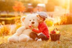 Petit garçon adorable avec son ami d'ours de nounours en parc sur le su Image libre de droits