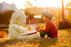 Petit garçon adorable avec son ami d'ours de nounours en parc sur le su Images libres de droits