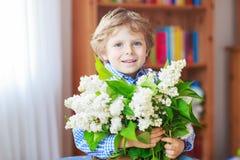 Petit garçon adorable d'enfant en bas âge avec la fleur lilas blanche de floraison Photos libres de droits