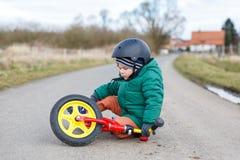 Petit garçon adorable d'enfant en bas âge triste au sujet de sa bicyclette cassée, sittin photos libres de droits