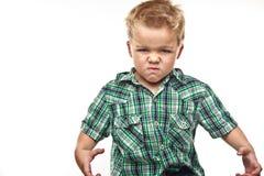 Petit garçon adorable semblant fâché. Photo stock