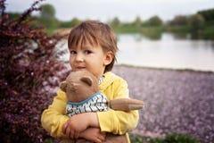 Petit garçon adorable, tenant l'ami de jouet en parc Photographie stock