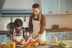 Petit garçon aidant son papa dans la cuisson Image stock