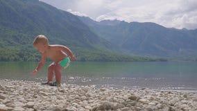 Petit garçon 2 ans dans l'eau du lac de montagne de forêt Vue arrière clips vidéos