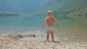 Petit garçon 2 ans dans l'eau du lac de montagne de forêt Vue arrière banque de vidéos