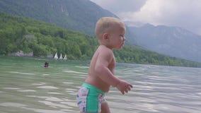 Petit garçon 2 ans dans l'eau du lac de montagne de forêt Vue du dos banque de vidéos