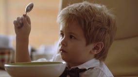 Petit garçon appréciant son gruau L'enfant drôle mangent du gruau avec du lait Aliment pour bébé, consommation de chéri clips vidéos