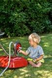 Petit garçon apprenant à utiliser le rochet Photo stock