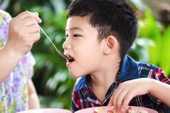 Petit garçon asiatique mangeant avec la nourriture de riz Photographie stock