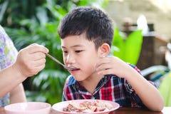 Petit garçon asiatique mangeant avec la nourriture de riz Images libres de droits