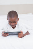Petit garçon assez de sourire à l'aide du comprimé numérique dans le lit photos stock