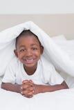Petit garçon assez de sourire dans le lit images libres de droits