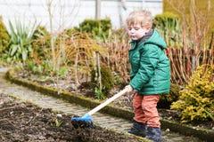 Petit garçon au printemps avec la houe de jardin, plantant et faisant du jardinage Photographie stock libre de droits
