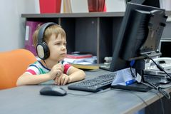 Petit garçon avec des écouteurs se reposant à l'ordinateur dans le bureau photos stock