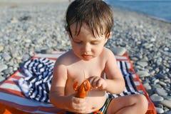 Petit garçon avec des écrevisses sur le bord de la mer Photo libre de droits