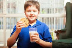Petit garçon avec du lait et un biscuit Image libre de droits