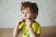 Petit garçon avec l'harmonica réserve vieux d'isolement par éducation de concept Concept de musique photo libre de droits