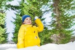 Petit garçon avec la boule de neige en parc derrière le mur Image stock