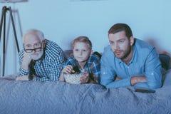 Petit garçon avec la cuvette de maïs éclaté, de son père et de grand-père se trouvant sur le lit et l'observation photographie stock libre de droits