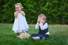 Petit garçon avec la fille et le lapin jouant dans l'herbe Photographie stock