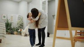 Petit garçon avec la maman en sa peinture pour bâtiments de salon sur le conseil avec des marqueurs un dessin du ` s d'enfant Fam banque de vidéos