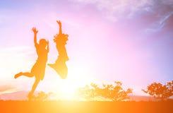 petit garçon avec la petite fille sautant au ciel et ayant le temps heureux Images libres de droits