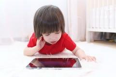 Petit garçon avec la tablette à la maison Photographie stock libre de droits