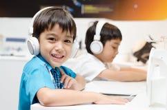 Petit garçon avec le casque dans la salle de classe Photographie stock libre de droits