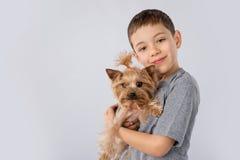 Petit garçon avec le chien de Yorkshire Terrier d'isolement sur le fond blanc Amitié d'animal familier d'enfants Photos stock