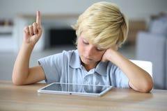 Petit garçon avec le comprimé soulevant la main à l'école Photo libre de droits