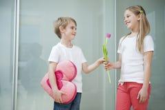 Petit garçon avec le coussin de forme de coeur donnant la fleur à la fille images stock