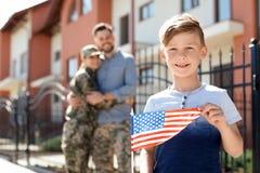 Petit garçon avec le drapeau américain et ses parents dans l'uniforme militaire, dehors Photos stock