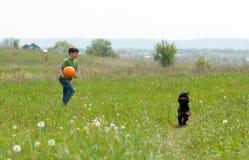 Petit garçon avec le football et son chien dehors Photo libre de droits