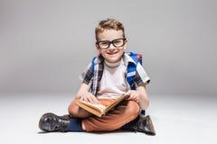 Petit garçon avec le livre de lecture de sac à dos dans la pose de yoga Photos stock